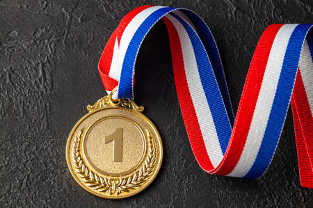 Gold medal with ribbons. Award for first place in the competition. Prize to the champion. Black background