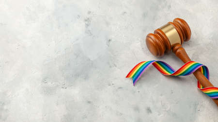 Judge gavel and rainbow ribbon of LGBT pride on gray background. Copy space for text Stock Photo