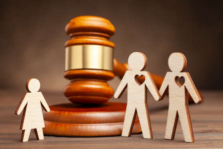 Child in a same-sex family. Adoption or sugrate motherhood in a gay family parental rights. Two gay men hold hands and a child and a judge hammer Stock Photo