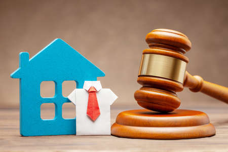 House with businessman in shirt and tie and judge gavel on brown background. Concept of selling a home by auction or sentence by right