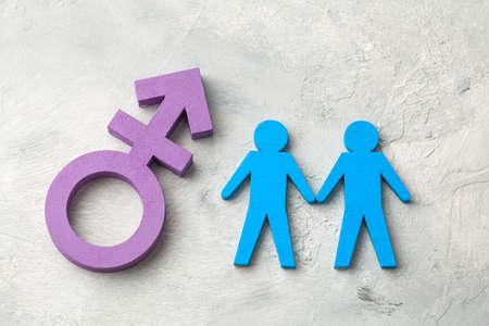 Gay couple holding hands on transgender symbol background