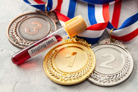 Doping test. Gold, silver and bronze medal and test tube with blood on a gray background Stock Photo
