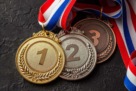 Gold, silver and bronze medal with ribbons. Award for first, second and third place in the competition. Prize to the champion. Black background Stock Photo