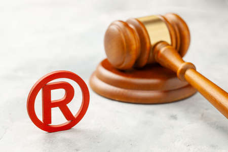 Judge gavel and red trademark sign grey Stock Photo