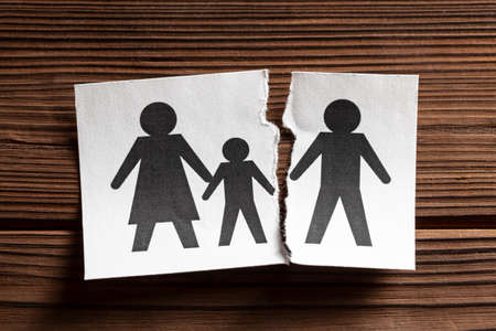 Breaking Relationships. Divorce in the family. The man left the family with children. Paper is torn in half with symbol of man and woman with child