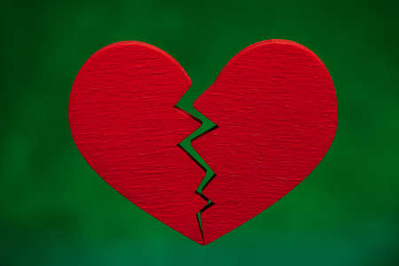 Broken heart. Crack in the red heart, Breaking the relationship. Green background.