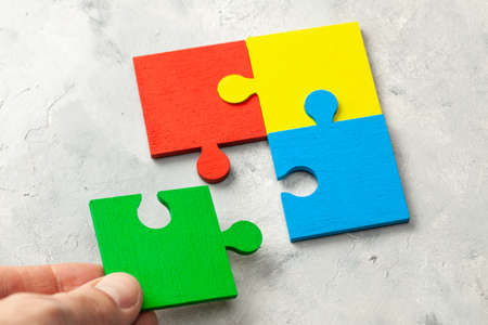 The colored part of the puzzle. Concept of team support and partner help. Male hand holding puzzle piece