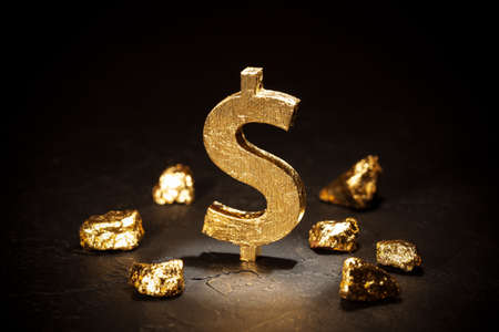 Gold dollar sign and gold nuggets on black background