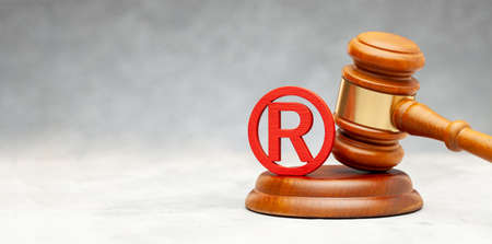 Judge gavel and red trademark sign on gray
