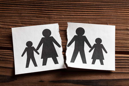 Breaking Relationships. Divorce in a family with children. Paper is torn in half with the symbol of father and wife with child