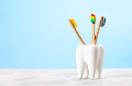 Many toothbrushes in a glass in the form of a tooth. Blue background. The concept of how to choose the right toothbrush Stock Photo