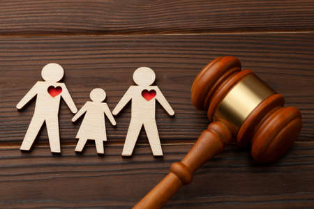 Adoption of a child by a same-sex couple. Judge gavel and the figures of two gay guys with a child hold hands Stock Photo