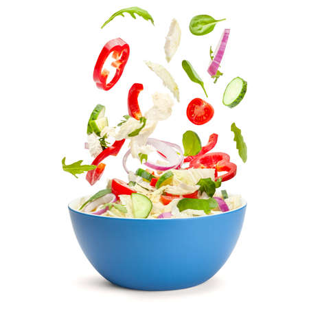 Vegetable salad in levitation. Fresh vegetarian salad of cucumbers, cabbage, cherry tomatoes, onions, peppers, spinach and arugula. Flying pieces of salad over a blue saucer isolated on white 免版税图像