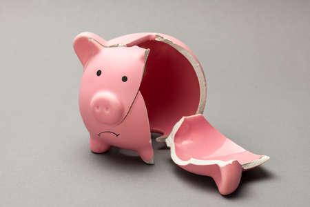 Broken piggy bank on gray background. sad face.
