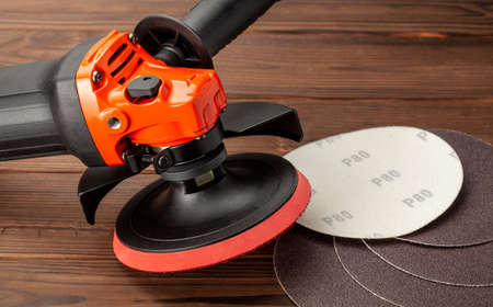 Angle grinder with sandpaper on wooden table