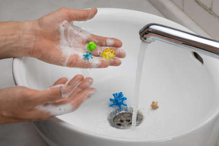Hand disinfection. A man washes his hands with soap and foam from viruses.