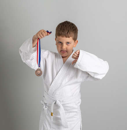 Boy in kimono holds the bronze medal for the third place in the competition. Not happy child shows tongue and thumbs down. Gray background