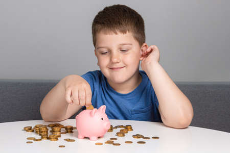 Child looks at the piggy bank and puts down coins. The boy smiles while investing