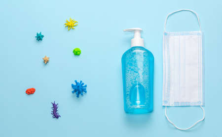 Various viruses and microbes on a blue background along with a medical mask and sanitizer. Top view
