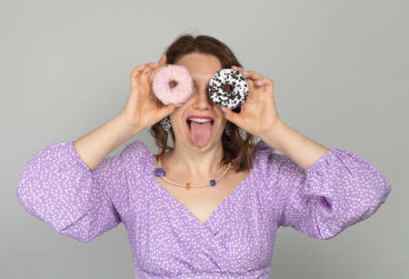 Girl holds donuts as glasses and shows her tongue in purple dress on gray background
