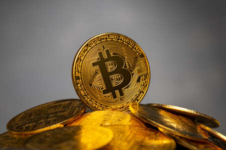 Bitcoin on a heap of cryptocurrency gold coins