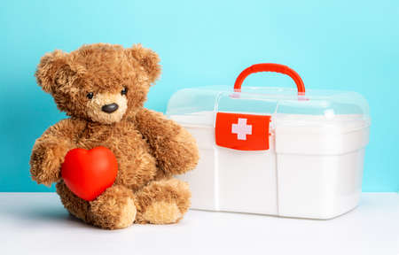 Teddy bear with heart and first aid kit on green background