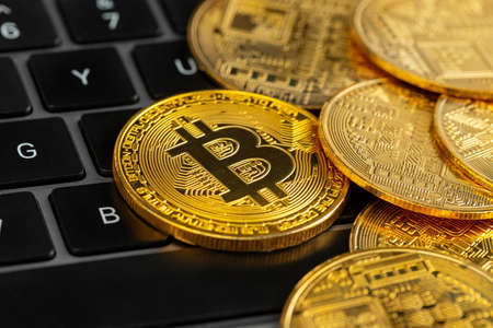 Gold bitcoin coins on laptop keyboard