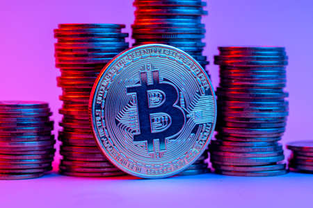 Bitcoin and stacks of coins in neon light
