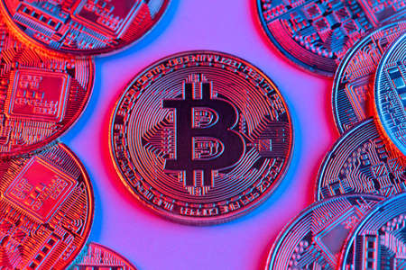 Bitcoin coins in neon light. The concept of the future belongs to cryptocurrency