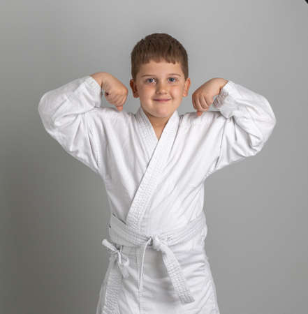 Boy in kimono holds his hands up shows his strength. Gray background