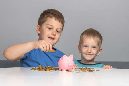 Two children smile and put coins in piggy bank