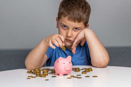 Sad boy lays down a coin in the piggy bank Stock Photo