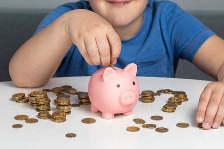 The child puts coins in the piggy bank Фото со стока