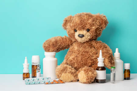 Medicines for children. Teddy bear and bottles with medicines, sprays, syrups, pills on a green background