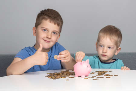 Two children put coins in piggy bank. Boys are investing in their future education. The boy smiles and shows thumbs up