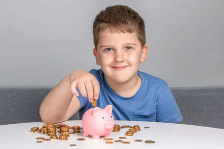 Boy smiles and puts coin in the piggy bank. The child invests in future education Stock Photo
