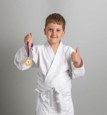 First place award. Boy in white kimono with gold furniture in hand. Satisfied child shows thumbs up. Gray background