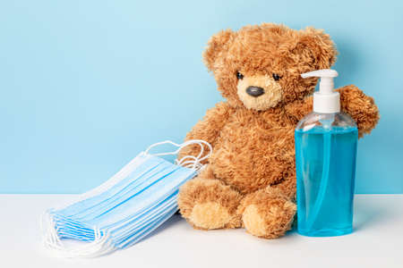 Protecting children from the virus. Teddy bear with sanitizer and medical masks Stock Photo