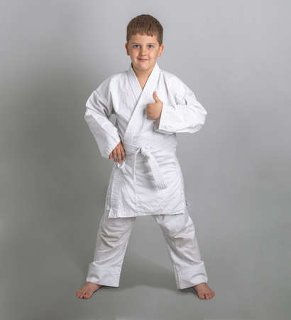 Boy in white kimono smiles and shows thumbs up. Gray background