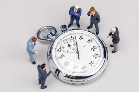 Stopwatch and businessmen in suits. Quick business meeting. Fast brainstorming