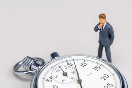 Businessman in a suit looks at the stopwatch. Fast business solution concept. Template Copy space for text