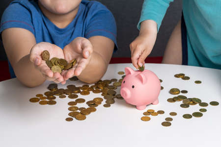 Two children put coins in piggy bank