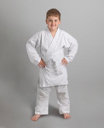 Boy in white kimono smiles on gray background