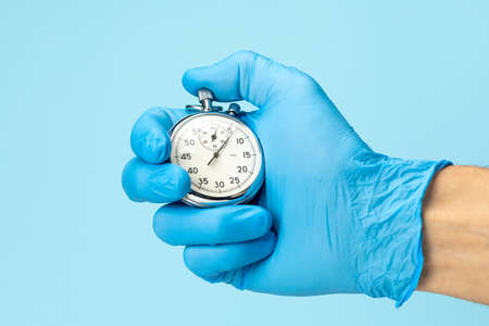 Doctor in glove holds stopwatch in his hand. Fast medical assistance and consultation concept