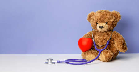 Teddy bear with a stethoscope and a heart on a purple background. Family doctor or pediatrician concept. Template Copy space for text Stock Photo