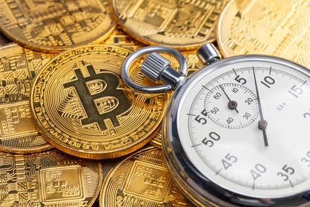 Stopwatch and bitcoin. Rapid growth of cryptocurrencies. Fast cryptocurrency transfer Stock Photo