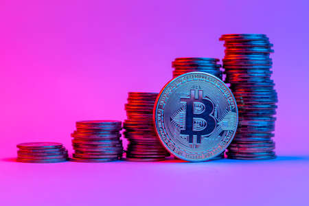 Bitcoin and stacks of coins steps up in neon light Stock Photo
