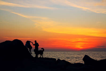 couple with dog at sunset on the reef photo