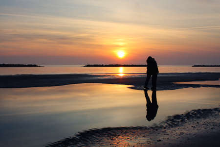 Couple kissing on the beach at dawn photo
