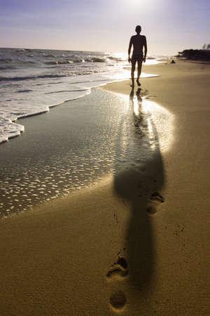 walking alone: hombre caminando en la playa Foto de archivo